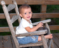 Cutie Pie. A little baby girl rocking in an old rocker on a deck with a smile on her face Royalty Free Stock Image