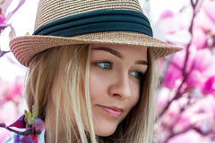 Cutie young blonde woman in hat looking away with flowers Stock Photo