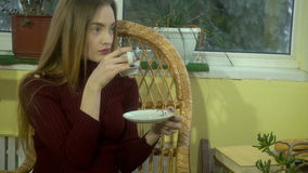 Cutie young girl with beautiful make up sits in wicker chair and drinks hot coffee looking out with window with snowfall stock footage