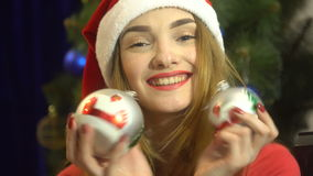Cutie young girl in santa hat with christmas toys in hands looking at the camera and smiling stock video