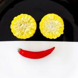 Cuties玉米和微笑辣椒 图库摄影