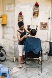 Cuting hår för vietnamesisk gatabarberareman av hans klient på gatan av Hanoi, Vietnam royaltyfri bild