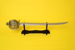 Cutlass. On stand blade, guard, and hilt isolated over yellow Stock Image