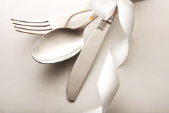 Cutlery. Knife, spoon and fork tied ribbon stock image
