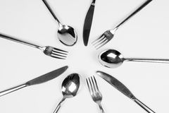 Cutlery around in circle. Silver cutlery, forks, knifes and spoons are around in circle on white background Royalty Free Stock Images