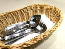 Cutlery in cane basket, cafe interior. A photograph showing some clean cutleries placed in a light brown rattan cane woven basket or small tray, for customers royalty free stock image