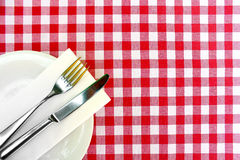 Cutlery on a checkered table cloth. A fork and a knife with a table napkin on a plate placed on a red and white checkered table cloth stock photos
