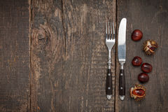 Cutlery and chestnut on a rustic wooden table Stock Photos