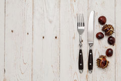 Cutlery and chestnut on a rustic wooden table Stock Images
