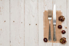Cutlery and chestnut on a rustic wooden table Stock Image