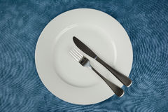 Cutlery and crockery. A knife and a fork on a white plate with a blue background Royalty Free Stock Photography