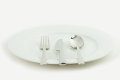 Cutlery and crockery. A white plate with a knife, fork and spoon on a white background Royalty Free Stock Photography