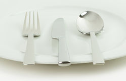 Cutlery and crockery. A white plate with a knife, fork and spoon on a white background Stock Photos