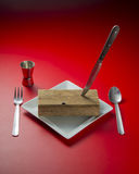 Cutlery. Delicious piece of wood with cutlery, plate, glass and a red background Stock Photo