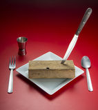 Cutlery. Delicious piece of wood with cutlery, plate, glass and a red background Royalty Free Stock Images