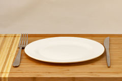 Cutlery empty plate, table knife and fork Royalty Free Stock Photography