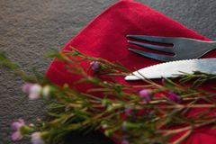 Cutlery and flora on red napkin. Close-up of cutlery and flora on red napkin Royalty Free Stock Image