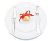 Cutlery fork knife plate and Easter golden egg. Stock Photos