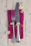Cutlery - fork and knife on purple napkin. Vintage cutlery - fork and knife on purple napkin on old wooden table with some daisies Stock Photography