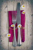 Cutlery - fork and knife on purple napkin in vintage stile. Cutlery - fork and knife on purple napkin on old wooden table with some daisies in vintage stile Royalty Free Stock Photo
