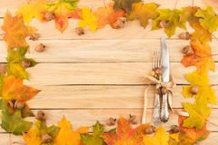 Cutlery in the frame made from maple leaves Royalty Free Stock Images