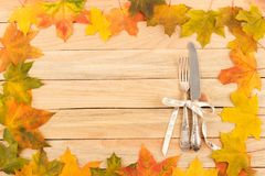 Cutlery in the frame made from maple leaves Royalty Free Stock Photo