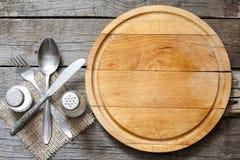 Cutlery i rocznik tnącej deski jedzenia pusty tło Obraz Stock