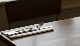 Cutlery. Knife and fork on a napkin on a restaurant table Stock Image