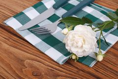 Cutlery knife and fork and a white rose Stock Image