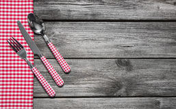 Cutlery: Knife, spoon and fork on wooden red checked background. Royalty Free Stock Photos