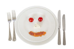 Cutlery. Knives, forks and plates. comic face made from tomatoes, cheese, red fish stock photo
