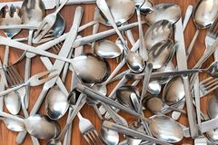 Shiny cutlery - background. Cutlery - knives, spoons and forks lie in disarray stock image