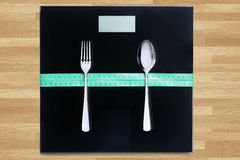Cutlery and measurement tool on wooden table Stock Images
