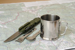 Cutlery and mug on map. Cutlery and mug on paper map Stock Photos