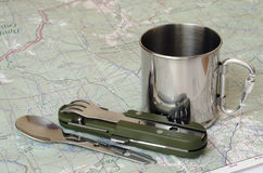 Cutlery and mug on map. Stainless cutlery and mug on paper map Royalty Free Stock Photography