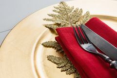 Cutlery with napkin and christmas decoration in a plate. Close-up of cutlery with napkin and christmas decoration in a plate Stock Photo