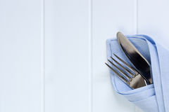 Cutlery in Napkin over Timber Background. Cutlery in pastel blue napkin over timber panel background.  Lots of room for text Stock Images