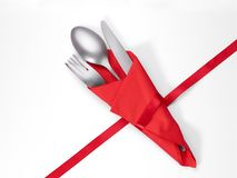 Cutlery and napkin with red ribbon isolated with clipping path. Cutlery and napkin with red ribbon. Isolated on white, clipping path included. Table setting and Stock Image