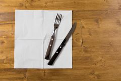Cutlery and paper napkin on wooden background stock images
