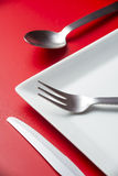 Cutlery. And plate with a red background Stock Images