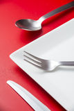 Cutlery. And plate with a red background Royalty Free Stock Image