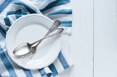 Cutlery, porcelain plate and white linen napkin. Vintage cutlery, porcelain plate and white linen napkin on wooden board, rustic style Royalty Free Stock Image