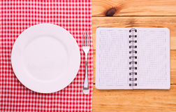 Cutlery red checkered tablecloth tartan on  wooden table top view. Royalty Free Stock Photo