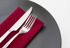 Cutlery on red napkin. With black plate Royalty Free Stock Photos