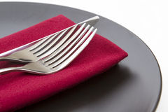 Cutlery on red napkin and plate Stock Photography