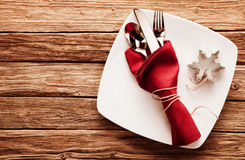 Cutlery in Red Napkin and Snowflake Cutter on Dish. High Angle View of Silver Cutlery Set Wrapped in Red Linen Napkin and Snowflake Shaped Cookie Cutter on royalty free stock photography