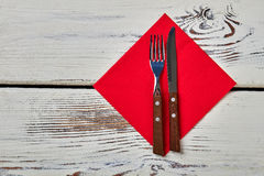Cutlery on red napkin. Napkin on wooden background. History of tableware spreading Royalty Free Stock Images