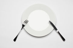 Cutlery and restaurant topic: Fork knife and white plate lying on a white table isolated in the studio top view. Cutlery and restaurant topic: Fork knife and Royalty Free Stock Photography