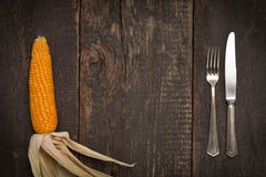 Cutlery on rustic old wooden table with corn on the cob Stock Image