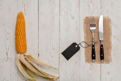 Cutlery on rustic old wooden table with corn on the cob Stock Photos